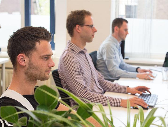 In een open kantoortuin werken developers en helpdeskmedewerkers zij-aan-zij.
